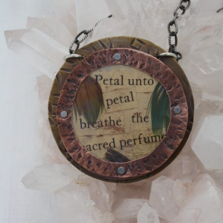 Mixed metal pendant with feather and text hung on crystals